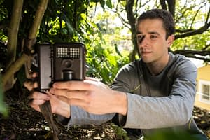 Caption of researcher setting up a camera trap